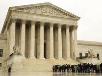 Personas hacen una fila en la lluvia afuera de la  Corte Suprema de Estados Unidos, en Washington, 29 de abril de 2014.  La Corte Suprema de Estados Unidos anunció el lunes que rechazó escuchar la apelación de Argentina sobre la orden judicial que la obliga a pagar unos 1.330 millones de dólares a tenedores de deuda en cesación de pagos. REUTERS/Gary Cameron