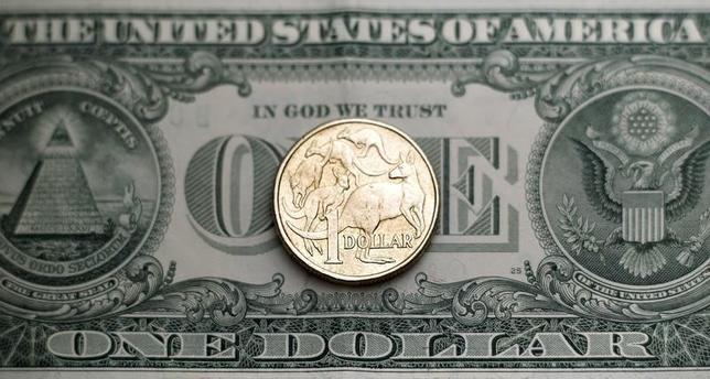An Australian one dollar coin stands on a U.S. one dollar note in this photo illustration taken in Sydney July 27, 2011. REUTERS/Tim Wimborne