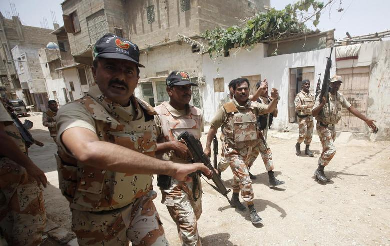 Paramilitary soldiers react as they ask members of the media to leave during their search in a neighbourhood, after a gunfire attack on a security academy run by the Airports Security Force (ASF) in Karachi June 10, 2014. REUTERS/Athar Hussain