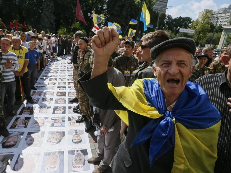 People protest near a ''corridor of shame'' made up of portraits of Ukrainian deputies from the Party of Regions and Communist Party laid out on the ground to press demands for parliament to be dissolved and early elections outside the assembly at the entrance to parliament in Kiev June 17, 2014.  REUTERS/Gleb Garanich