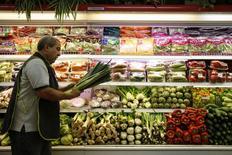 Un trabajador sostiene puerros en un supermercado en Caracas, 13 de junio de 2014. Polar, la mayor empresa privada de Venezuela, detuvo la producción de su planta de envasado de bebidas ante la falta de materia prima para elaborar latas, dijeron trabajadores citados por medios locales el martes. REUTERS/Carlos Garcia Rawlins