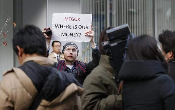 Kolin Burges, a self-styled cryptocurrency trader and former software engineer from London, holds up a placard to protest against Mt. Gox, in front of the building where the digital marketplace operator was formerly housed in Tokyo February 26, 2014. Japanese authorities are looking into the abrupt closure of Mt. Gox, the top government spokesman said on Wednesday in Tokyo's first official reaction to the turmoil at what was the world's biggest exchange for bitcoin virtual currency.    REUTERS/Toru Hanai (JAPAN - Tags: BUSINESS SCIENCE TECHNOLOGY CIVIL UNREST) - RTR3FQ9C