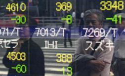 Отражение людей в экране с фондовыми котировками у брокерской конторы в Токио, 16 мая 2014 года. Азиатские фондовые рынки, кроме Японии, снизились в среду в ожидании решений ФРС и под влиянием отдельных отраслей. REUTERS/Yuya Shino