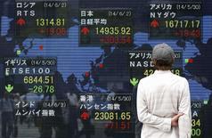 Un peatón mira una pantalla electrónica afuera de una bolsa en Tokio, 2 de junio de 2014.  El índice Nikkei de la bolsa de Tokio subió el miércoles a un máximo en una semana y media luego de que el yen se debilitó ante unos sólidos datos de precios al consumidor en Estados Unidos.  REUTERS/Yuya Shino
