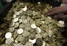 Десятирублевые монеты на монетном дворе в Санкт-Петербурге 9 февраля 2010 года. Рубль подрос к доллару и бивалютной корзине при открытии биржевой сессии четверга в русле тенденций спроса на риск после заседания ФРС и перед завтрашней уплатой НДС, а также в преддверии основного для экспортеров налога, НДПИ, 25 июня. REUTERS/Alexander Demianchuk