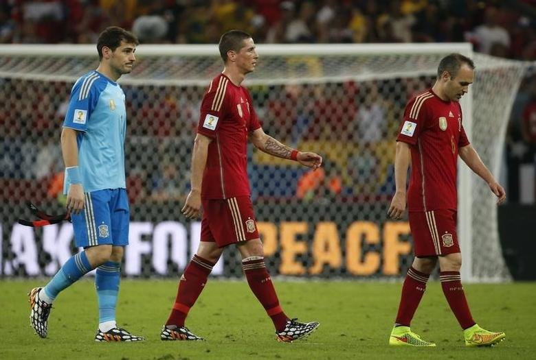 Spain's goalkeeper Iker Casillas (L),  Andres Iniesta (C) and Fernando Torres walk off the field after their 2014 World Cup Group B soccer match against Chile at the Maracana stadium in Rio de Janeiro June 18, 2014.       REUTERS/Jorge Silva