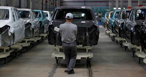 Un trabajador transporta el armazón de un auto Datsun Go+ a una ensamblería en la fábrica de Nissan Indonesia, en Purwakarta, 8 mayo de 2014.  La confianza de los fabricantes japoneses se mantuvo estable en junio, mientras que el estado de ánimo en el sector de servicios repuntó frente al mes anterior, lo que representa una señal alentadora para la economía. REUTERS/Beawiharta