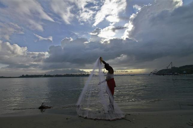 A fisherman arranges his fishing net at a beach against the backdrop of pre-monsoon clouds in of Kochi June 5, 2014. REUTERS/Sivaram V.
