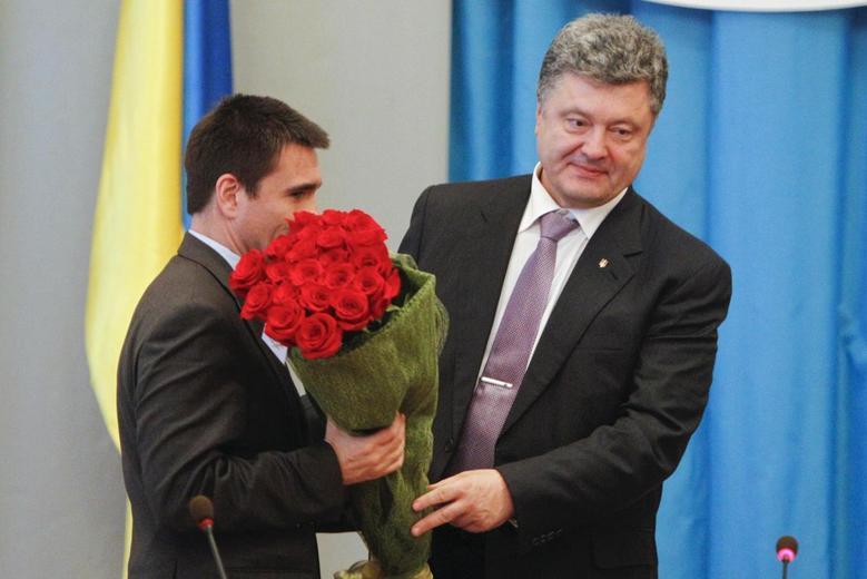 Ukraine's President Petro Poroshenko (R) presents flowers to newly appointed Foreign Minister Pavlo Klimkin during Klimkin's presentation to employees of the Ministry of Foreign Affairs, in Kiev June 19, 2014. REUTERS/Valentyn Ogirenko