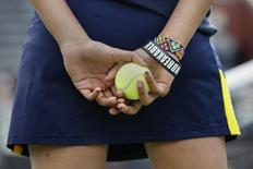 A girl holds a tennis ball during ballpersons tryouts at the USTA Billie Jean King National Tennis Center in the Queens borough of New York June 19, 2014.  REUTERS/Shannon Stapleton