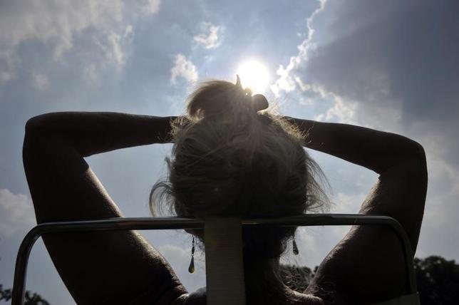 6月19日、日焼けの習慣は皮膚がんのリスクを高めるだけでなく、日焼け行為そのものに中毒になる危険性があることが、明らかになった。写真は昨年7月、ベルギーの公園で日光浴をする女性(2014年 ロイター/Eric Vidal)