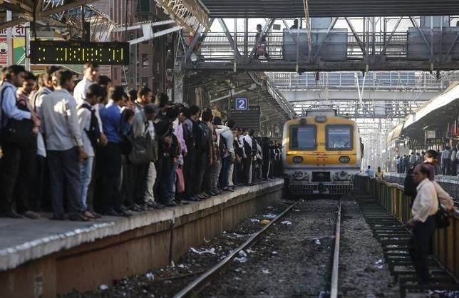 Commuters wait on a crowded railway platform as a train enters a suburban station in Mumbai February 12, 2014. REUTERS/Danish Siddiqui/Files