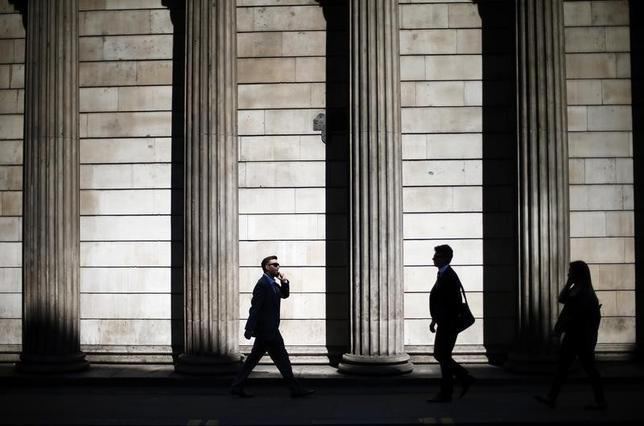 People are silhouetted on a sunny morning as they walk past the columns of the Bank of England in the City of London, May 19, 2014.  REUTERS/Andrew Winning