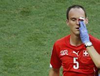 Steve von Bergen, da seleção da Suíça, é ajudado pelo médico da equipe durante partida contra a França, em Salvador. 20/06/2014. REUTERS/Fabrizio Bensch