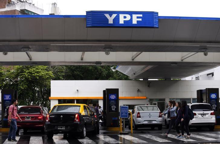 People walk past a YPF petrol station in Buenos Aires November 26, 2013.   REUTERS/Marcos Brindicci