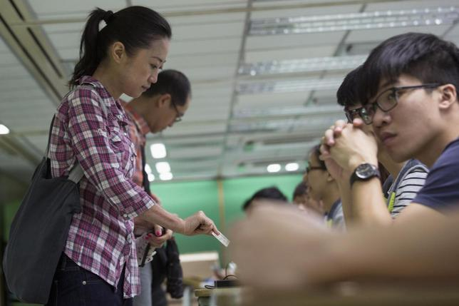 A woman presents her ID card to a poll assistant during a civil referendum held by the Occupy Central organisers at polling station in Hong Kong June 22, 2014.  REUTERS/Tyrone Siu