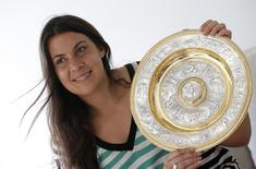 Wimbledon women's singles tennis champion Marion Bartoli of France holds her trophy as she attends an interview with Reuters in Boulogne-Billancourt near Paris, July 9, 2013.   REUTERS/Christian Hartmann