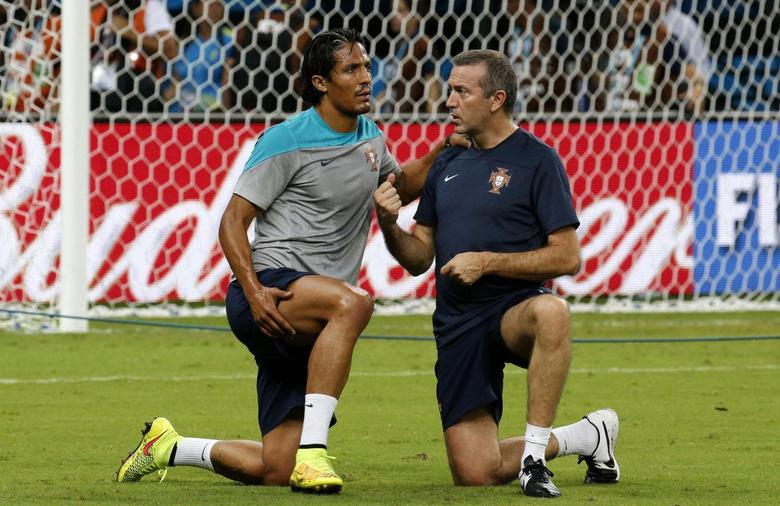 Portugal's defender Bruno Alves (L) chats with his physician during a training session, ahead of their 2014 World Cup match against the U.S. at Arena da Amazonia stadium in Manaus June 21, 2014. REUTERS/Siphiwe Sibeko