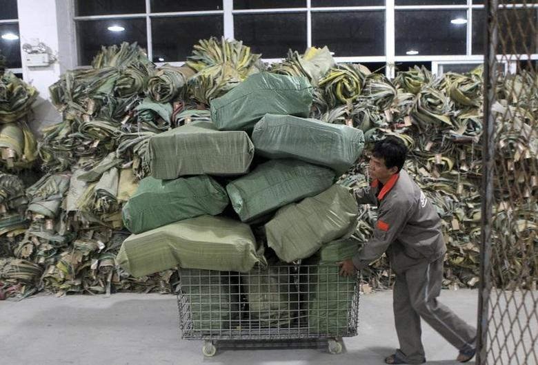A worker pushes a cart filled with packages at a logistics hub in Fuzhou, Fujian province November 13, 2012. REUTERS/Stringer