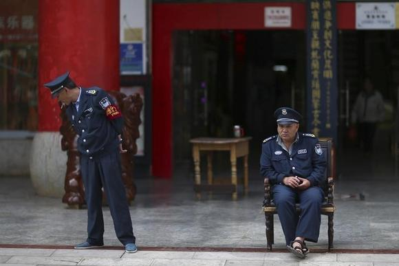 Security guards are seen on duty in front of a jewellery store in Kunming, Yunnan province May 8, 2014. REUTERS/Wong Campion/Files