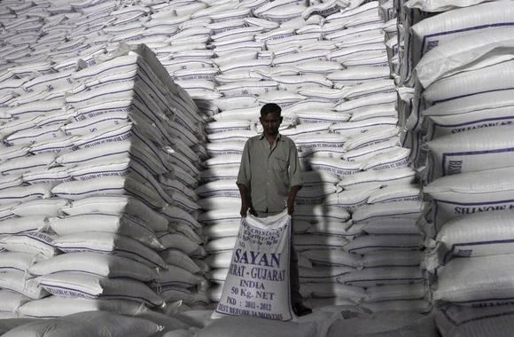 A worker shifts a sack of sugar at a godown inside a sugar factory at Sanyan village in Gujarat April 23, 2012. REUTERS/Amit Dave/Files