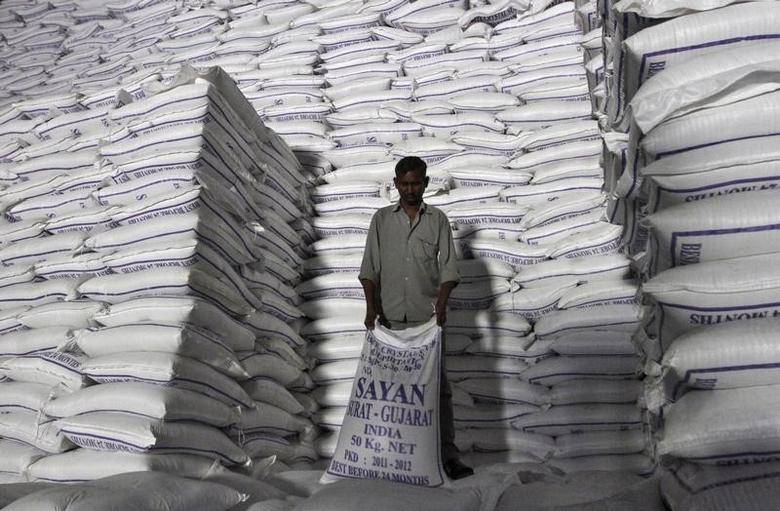 A worker shifts a sack of sugar at a godown inside a sugar factory at Sanyan village in Gujarat April 23, 2012. REUTERS/Amit Dave/Files