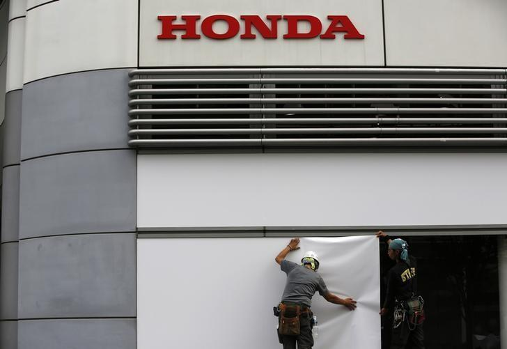 Workers Stand Under The Logo Of Honda Motor Co Outside Companys Headquarters In Tokyo