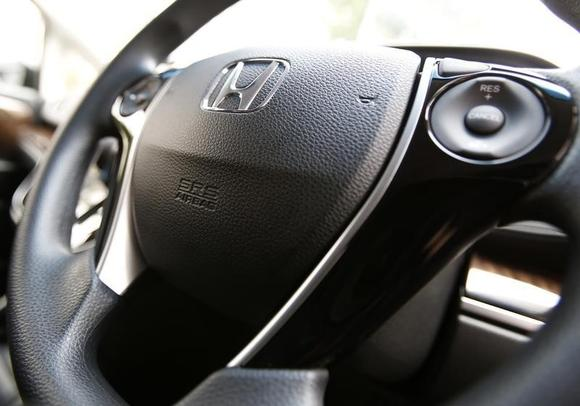 The logo of Honda Motor Co and an airbag logo are seen on a steering wheel of a car displayed at the company's showroom in Tokyo June 17, 2014. REUTERS/Yuya Shino