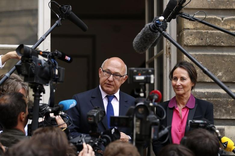 French Ecology, Sustainable Development and Energy Minister Segolene Royal (R) and Finance Minister Michel Sapin speak to the journalists after a conference about the financing of energy transition in Paris June 23, 2014. REUTERS/Benoit Tessier