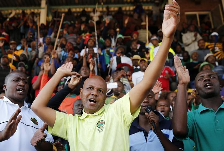 President of South Africa's Association of Mine workers and Construction Union (AMCU) Joseph Mathunjwa (C) sings before addressing the Lonmin strikers at the Wonderkop stadium in Nkaneng township outside the Lonmin mine in Rustenburg May 14, 2014.   REUTERS/Siphiwe Sibeko