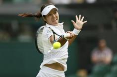 Li Na of China hits a return to Paula Kania of Poland in their women's singles tennis match at the Wimbledon Tennis Championships, in London June 23, 2014.         REUTERS/Stefan Wermuth