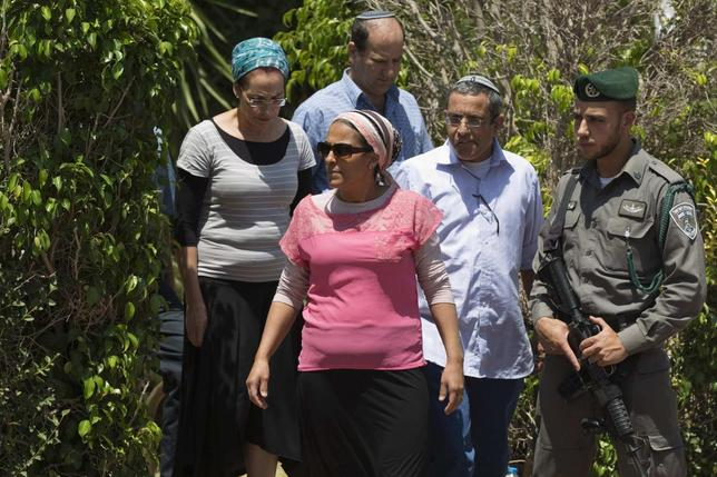 Iris and Uri Yifrah (foreground), Bat-Galim Shaer (back L), and Avi Fraenkel (back R), the respective parents of missing Israeli teens Eyal, Gil-Ad and Naftali, walk outside the Shaer family home in the West Bank Jewish settlement of Talmon June 23, 2014.  REUTERS/Finbarr O'Reilly