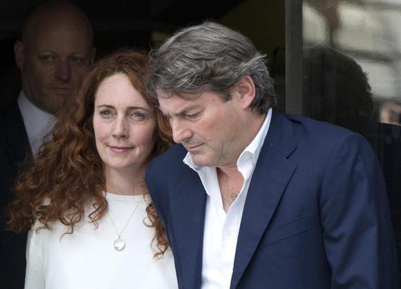 Former News International chief executive Rebekah Brooks and her husband Charlie leave the Old Bailey courthouse in London June 24, 2014. REUTERS/Neil Hall