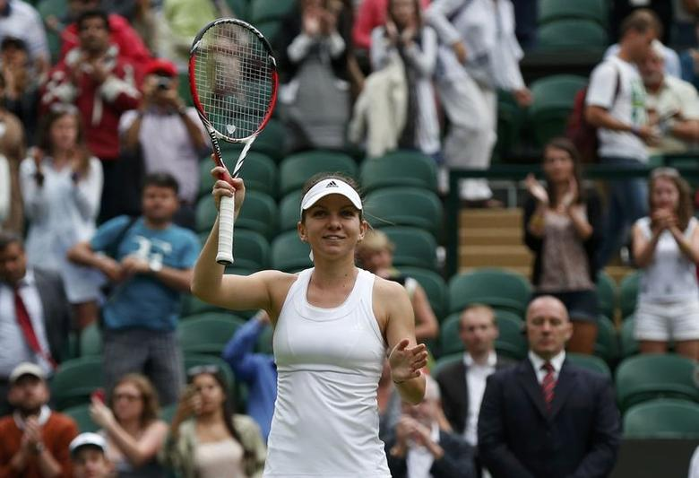 Simona Halep of Romania reacts after defeating Teliana Pereira of Brazil in their women's singles tennis match at the Wimbledon Tennis Championships, in London June 24, 2014. REUTERS/Suzanne Plunkett