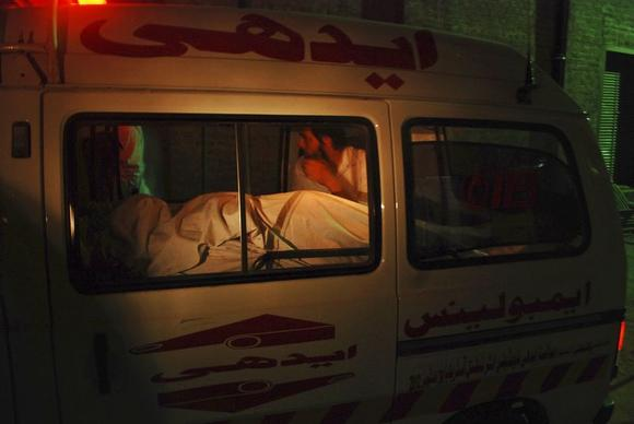 A man sits beside the body of a woman who was killed on board a Pakistan International Airlines (PIA) plane, as the ambulance carrying them arrives at a hospital in Peshawar early June 25, 2014. REUTERS/Khuram Parvez