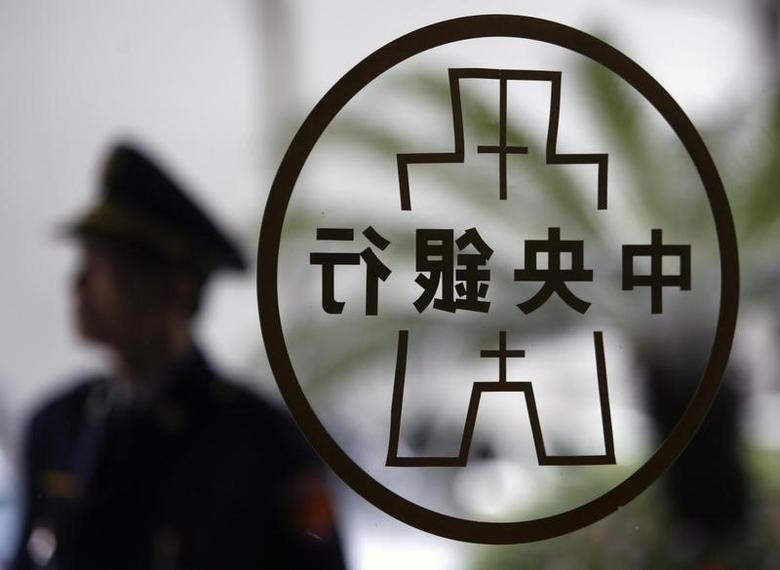 A security guard stands in front of the Taiwan Central Bank logo in Taipei March 26, 2009.  REUTERS/Nicky Loh