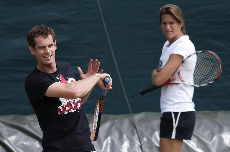 Andy Murray of Britain, watched by Amelie Mauresmo, his newly appointed coach, hits a return during a training session at the Wimbledon Tennis Championships, in London June 24, 2014.         REUTERS/Suzanne Plunkett