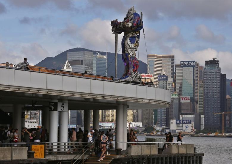 A figure of Transformer is displayed on top of a pier outside the Hong Kong Cultural Centre in Hong Kong June 18, 2014. REUTERS/Bobby Yip