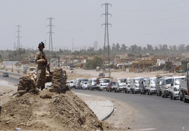 A member of the Iraqi security forces stands guard along a road during an intensive security deployment west of Baghdad, June 24, 2014. REUTERS/Ahmed Saad
