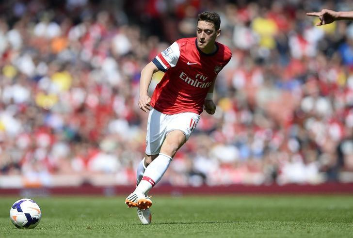 Arsenal's Mesut Ozil passes the ball during their English Premier League soccer match against West Bromwich Albion at the Emirates stadium in London May 4, 2014.    REUTERS/Dylan Martinez