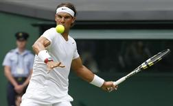 Rafael Nadal of Spain hits a return to Martin Klizan of Slovakia during their men's singles tennis match at the Wimbledon Tennis Championships, in London June 24, 2014.           REUTERS/Suzanne Plunkett