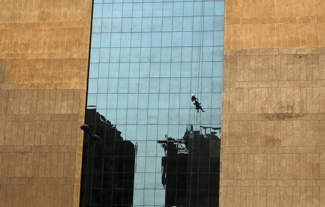 A worker cleans the glass exterior of a building in the commercial hub of New Delhi February 26, 2013. REUTERS/Adnan Abidi/Files