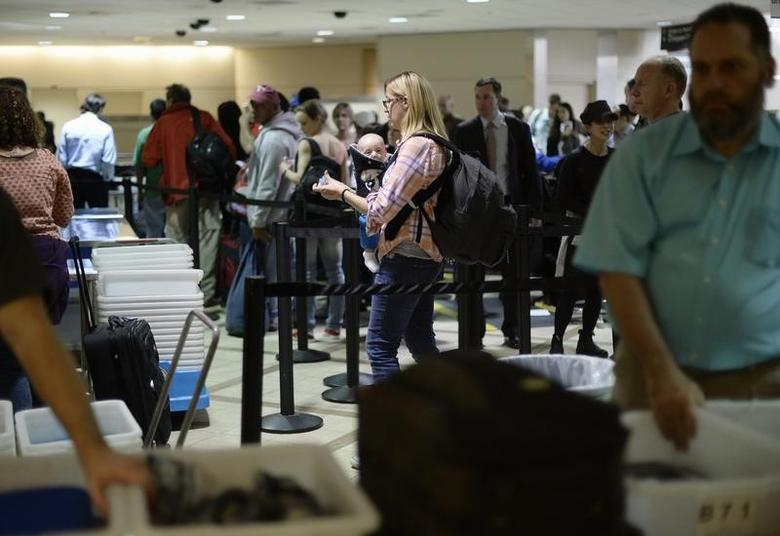 An airline passenger and her baby wait in line before passing through Transportation Security Administration (TSA) security checkpoint at Los Angeles International Airport in Los Angeles, California February 20, 2014.  REUTERS/Kevork Djansezian