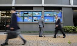 Un hombre mira el promedio del Nikkei japonés y varios valores de otros países afuera de la bolsa de Tokio, 16 de abril de 2014. Las bolsas en Asia subían el jueves luego de que unos datos que revelaron un débil crecimiento en Estados Unidos parecieron aplazar adicionalmente el día en que podrían subir las tasas de interés, lo que llevaba a los inversores a poner fondos en los activos de mayor riesgo en una búsqueda de ganancias. REUTERS/Toru Hanai