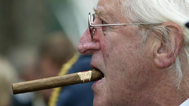 Disgraced British entertainer Jimmy Savile is seen arriving at the unveiling of a new monument, commemorating the fighter pilots who fought in the Battle of Britain, in London in this September 18, 2005 file photograph.REUTERS/Paul Hackett/Files