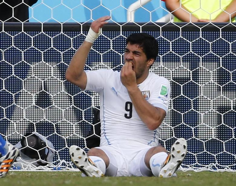 Uruguay's Luis Suarez holds his teeth during the 2014 World Cup Group D soccer match between Uruguay and Italy at the Dunas arena in Natal June 24, 2014. REUTERS/Yves Herman