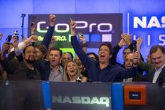 Nick Woodman (au centre), fondateur et directeur général de GoPro, marque le début de la séance du Nasdaq, à New York. Le fabricant des caméras miniatures prisées des amateurs de sports extrêmes a parfaitement réussi ses débuts en Bourse, le titre ayant gagné jusqu'à 38% sur le Nasdaq lors de sa première séance de cotation jeudi. /Photo prise le 26 juin 2014/REUTERS/Mike Segar