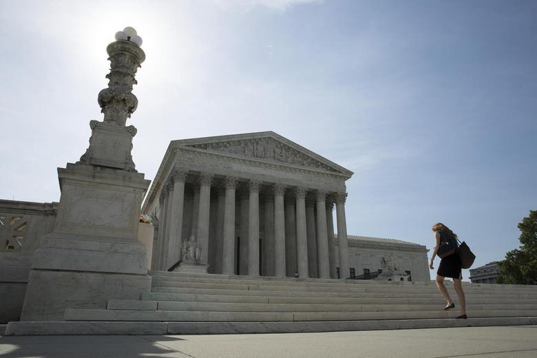 A woman walks to the Supreme Court in Washington June 19, 2014.  The U.S. Supreme Court on Thursday ruled that implementing an abstract idea using a computer does not make an invention patent eligible.     REUTERS/Joshua Roberts