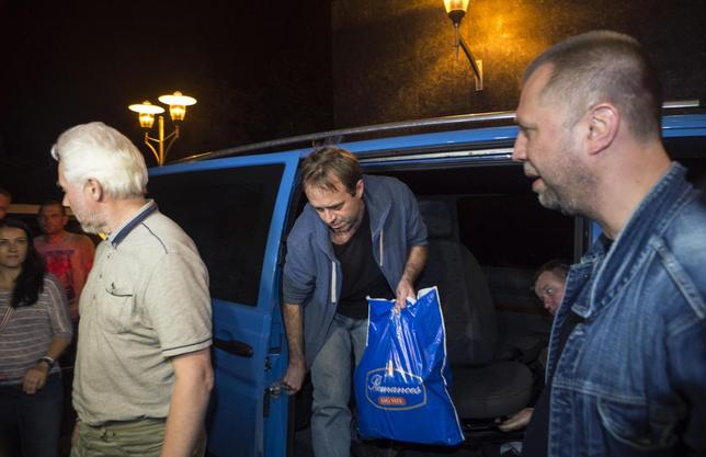 Unidentified members of OSCE Special Monitoring Mission in Ukraine get out of a vehicle next to Alexander Borodai (R), Prime Minister of the self proclaimed ''Donetsk People's Republic'', on arrival at the city of Donetsk after being released from captivity, June 27, 2014.  REUTERS/Shamil Zhumatov