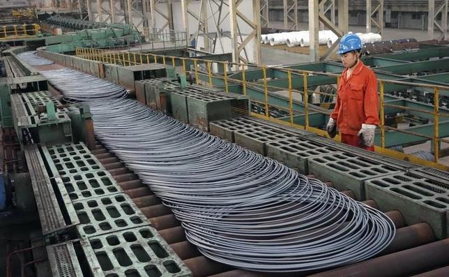 A labourer looks at steel coils next to a production line of Dongbei Special Steel Group Co., Ltd., in Dalian, Liaoning province September 27, 2013.  REUTERS/China Daily